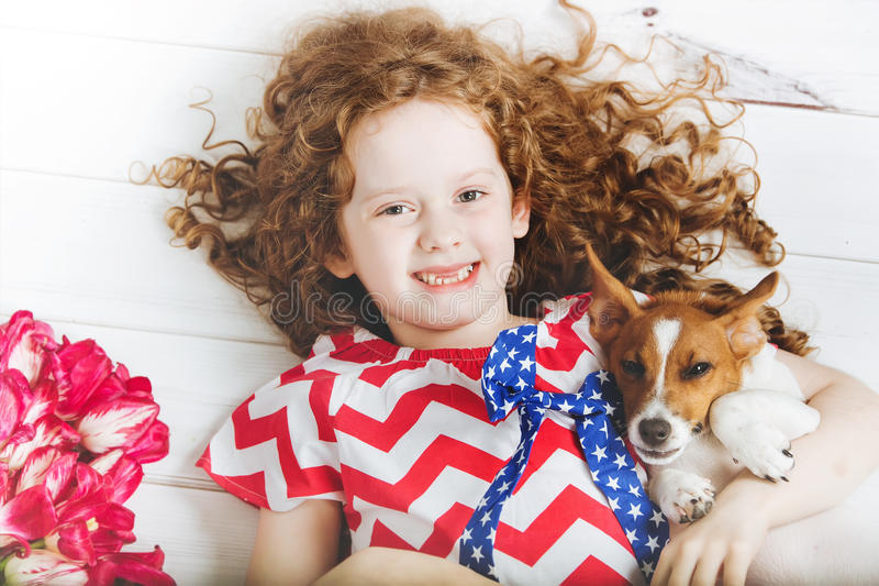 Laughing toothless girl hugging a puppy. royalty free stock photos