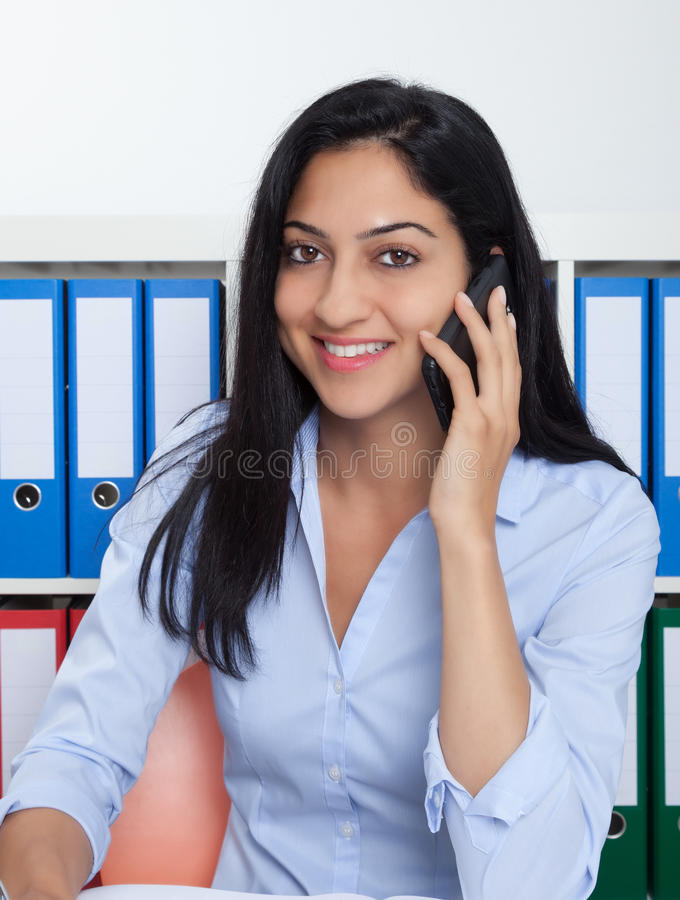 Laughing turkish businesswoman with phone at office royalty free stock image
