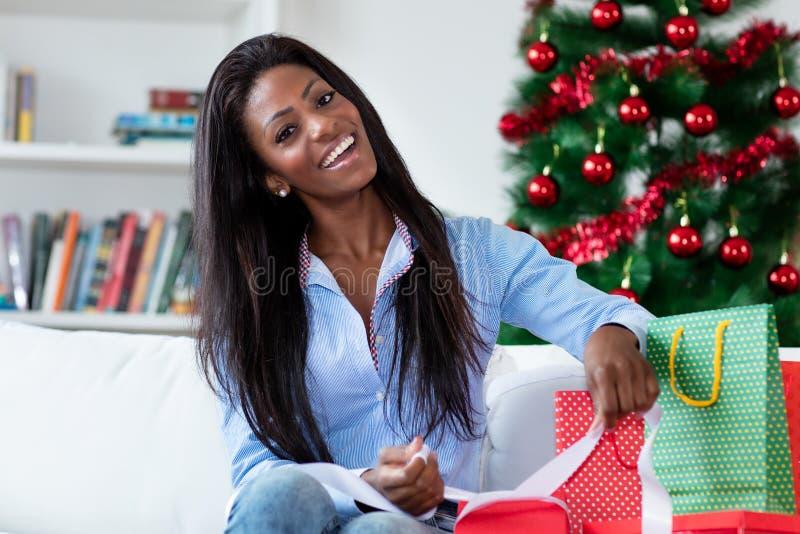 Laughing van een afrikaanse amerikaanse vrouw die geschenken voorbereidt voor kerstmis stock afbeeldingen