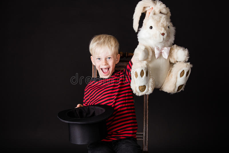 Laughing vivacious little boy magician royalty free stock photo