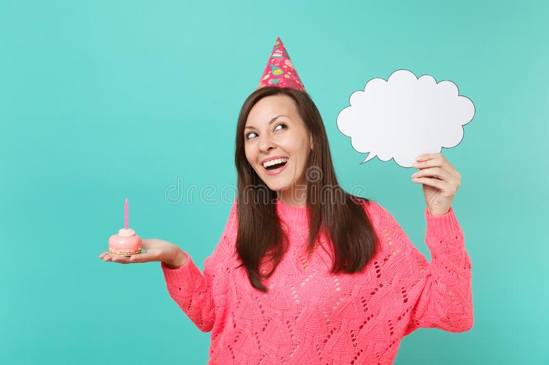 Laughing woman in birthday hat looking up hold cake with candle, empty blank Say cloud, speech bubble for promotional. Content isolated on blue background royalty free stock photo
