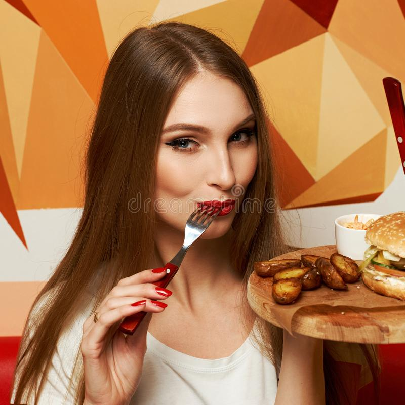 Laughing woman eating burger. Happy attractive woman holding fork and round wooden plate with appetizing burger and fried potato. Beautiful joyful female model stock photos