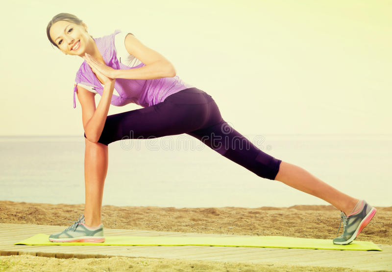 Download Laughing Woman Exercising Yoga Poses On Beach Stock Photo - Image: 83701865