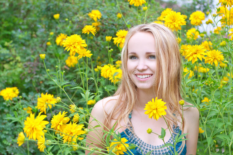 Laughing woman among flowers royalty free stock photo