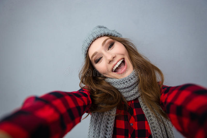 Laughing woman in hat and scarf making selfie photo. Portrait of a laughing woman in hat and scarf making selfie photo over gray background royalty free stock photo
