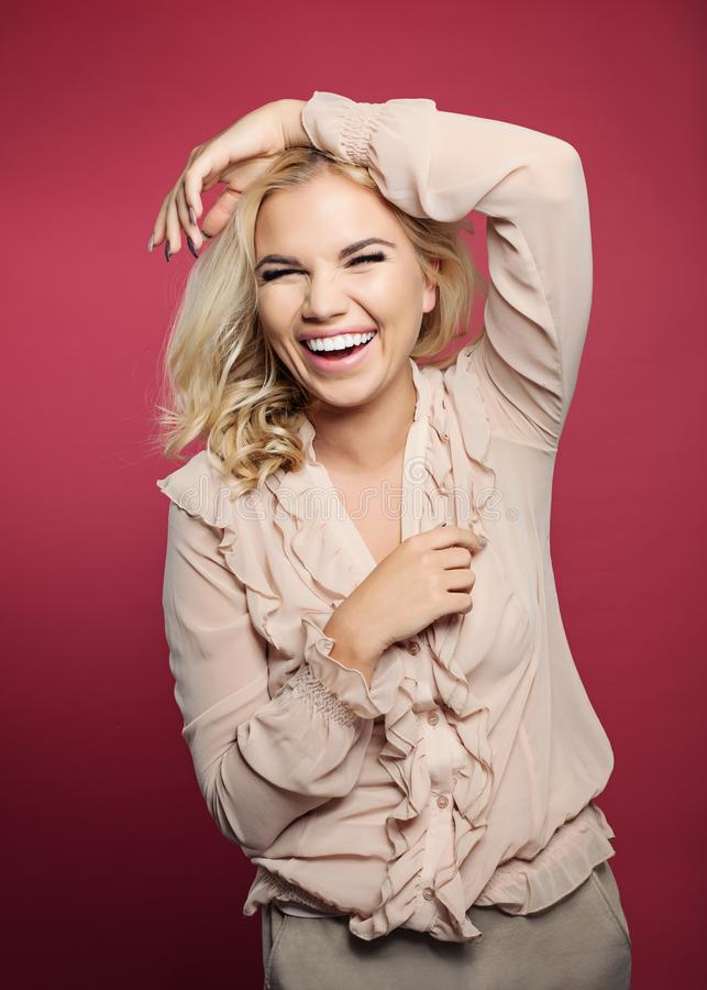 Laughing woman having fun on colorful bright pink background.  royalty free stock photography