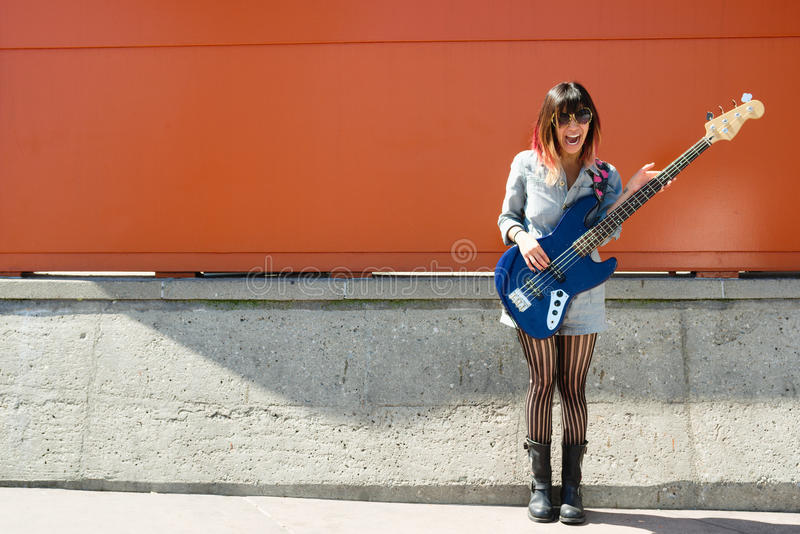 Download Laughing Woman Holding Blue Bass Guitar Outside Stock Photo