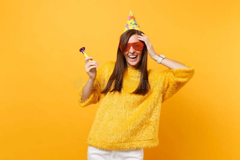 Laughing woman in orange funny glasses, birthday hat with playing pipe putting hand on head celebrating isolated on. Yellow background. People sincere emotions royalty free stock photos