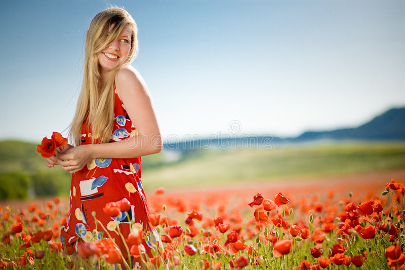 Laughing woman in poppy field royalty free stock image