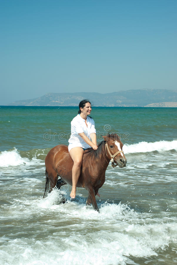 Laughing woman rides horse in water sea royalty free stock photography