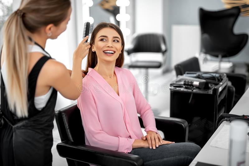 Laughing woman is sitting in armchair in beauty salon. Professional stylist holding comb and making hair styling for happy lady stock images