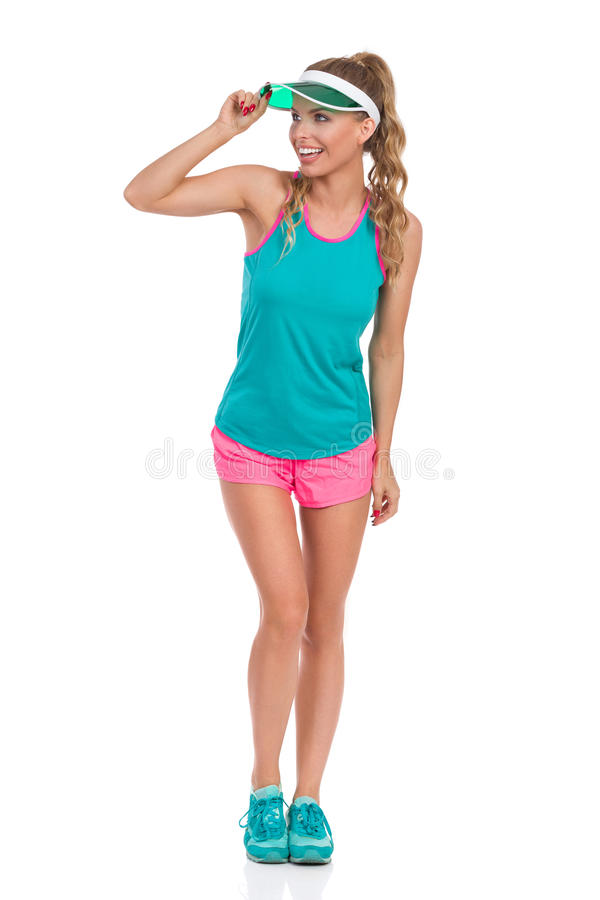 Laughing Woman In Sports Outfit And Sun Visor. Smiling beautiful young woman in pink shorts, green tank top, sneakers and sun visor standing and looking away royalty free stock photos
