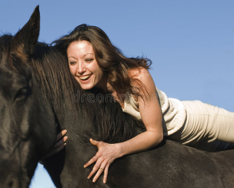 Laughing woman and stallion royalty free stock image