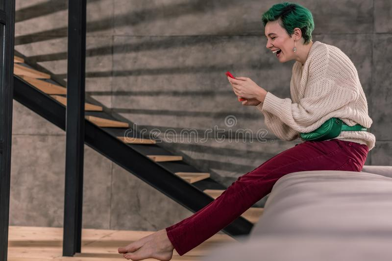 Laughing woman wearing bright trousers feeling cheerful. Laughing woman. Laughing woman wearing bright trousers feeling cheerful after seeing funny post stock photos