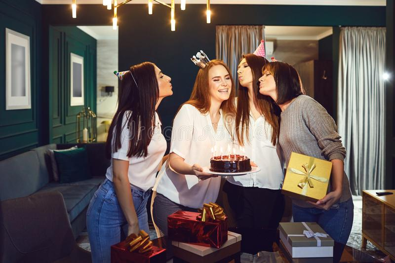 Laughing women celebrating birthday together. Stylish young women with cake and gifts congratulating charming friend on birthday having party at home stock images
