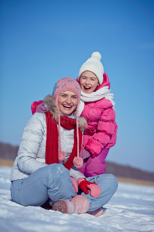 Laughing. Women and little girl in winterwear looking at camera royalty free stock photos