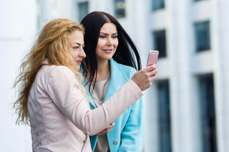 Laughing women looking at phone stock photography