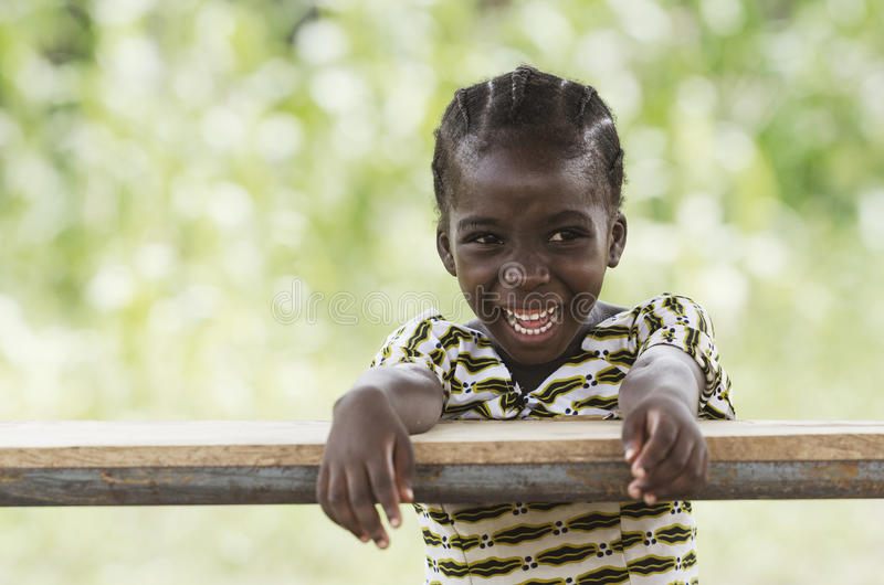 Laughing young African girl sitting in her desk stock photo