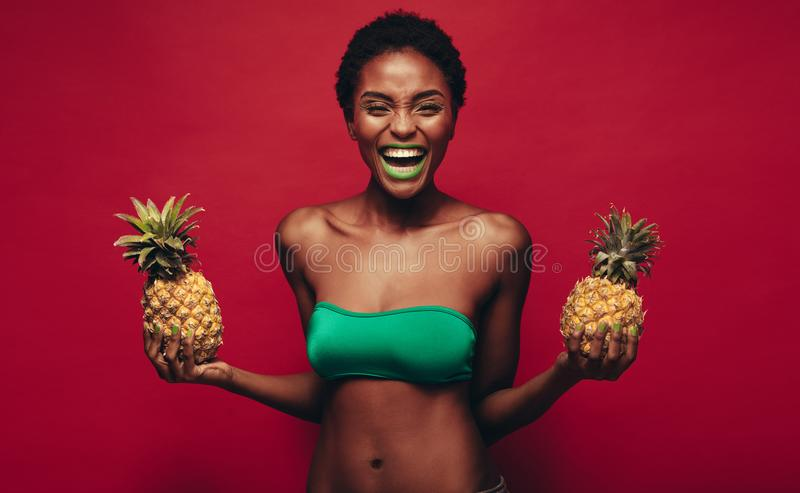 Laughing african woman with pineapples royalty free stock photos
