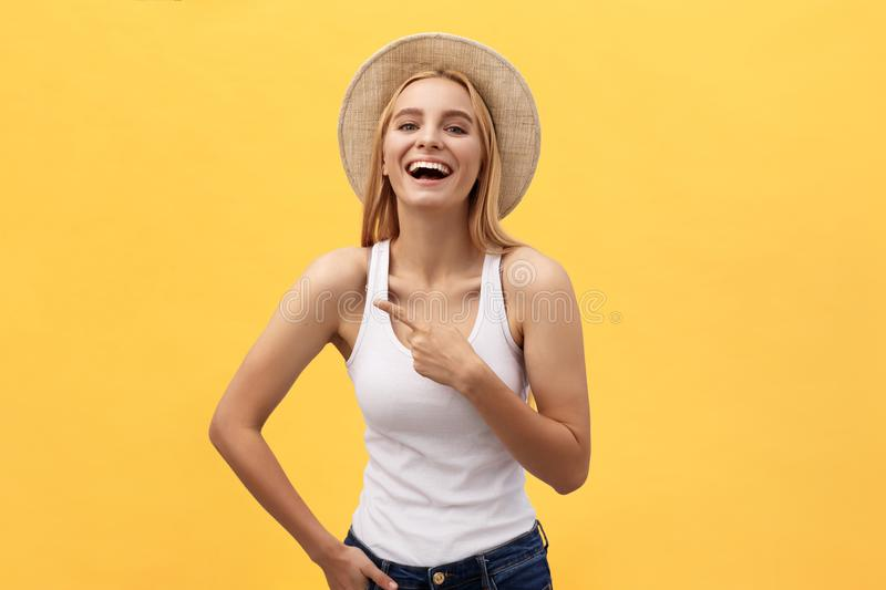 Laughing young beautiful woman in t-shirt looking and pointing away with finger over yellow background royalty free stock photography