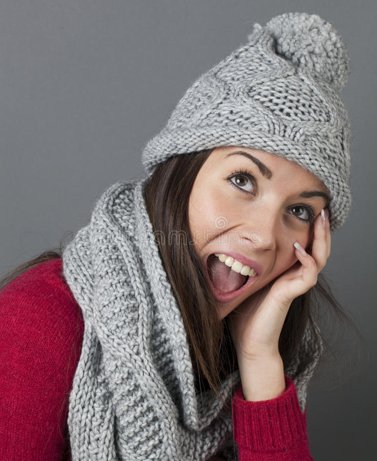 Laughing young blonde woman smiling for warmth and cozyness in winter royalty free stock image