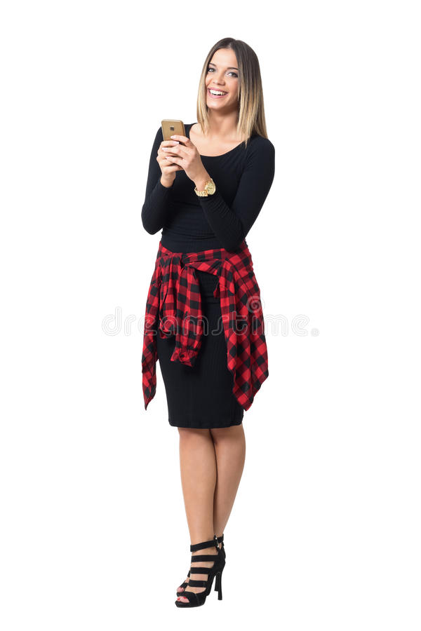 Laughing young elegant woman reading jokes on mobile phone. Full body length isolated over white studio background stock photography