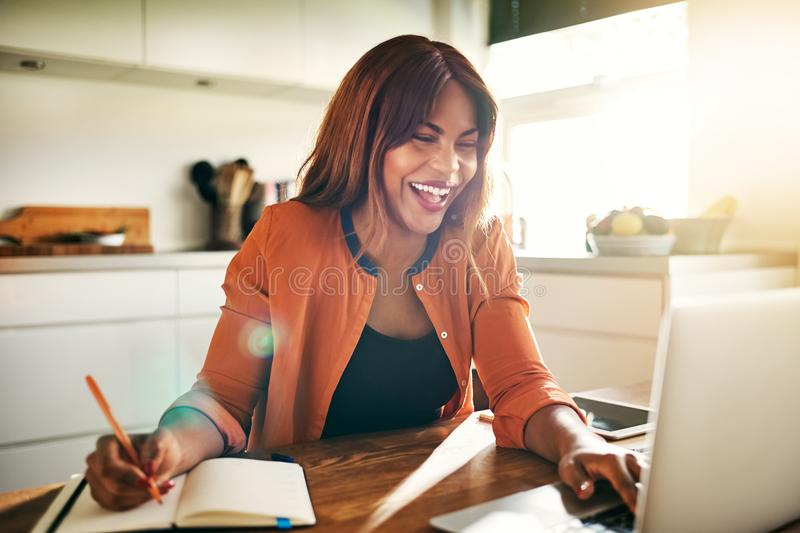 Laughing young female entrepreneur working online in her kitchen royalty free stock photography