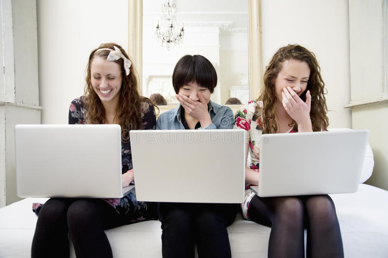 Laughing Young Female Friends Sitting On Sofa Royalty Free Stock Photography
