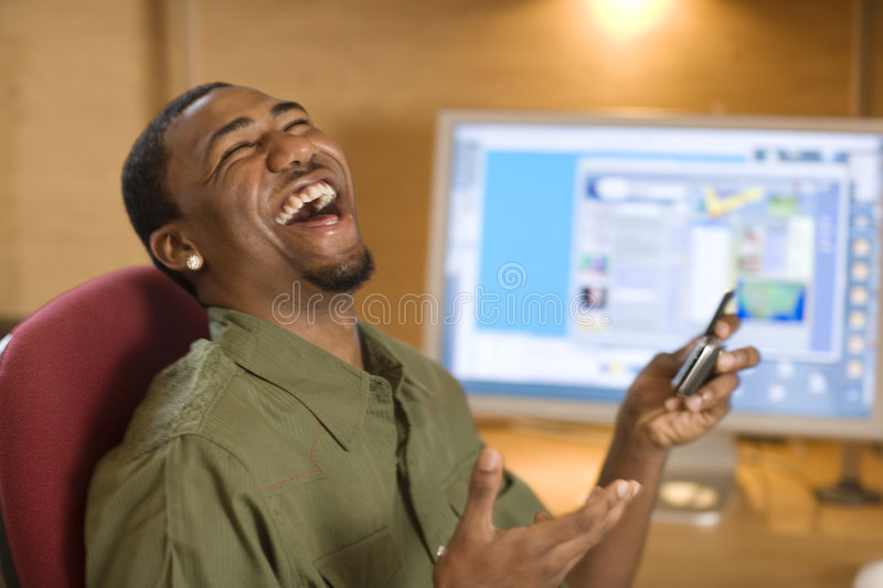 Laughing young man with cell phone and computer stock photography