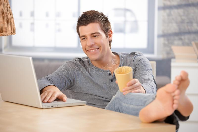 Laughing young man using computer at home. Laughing young man enjoying using laptop computer at home, holding tea cup, looking at screen with bare feet on table
