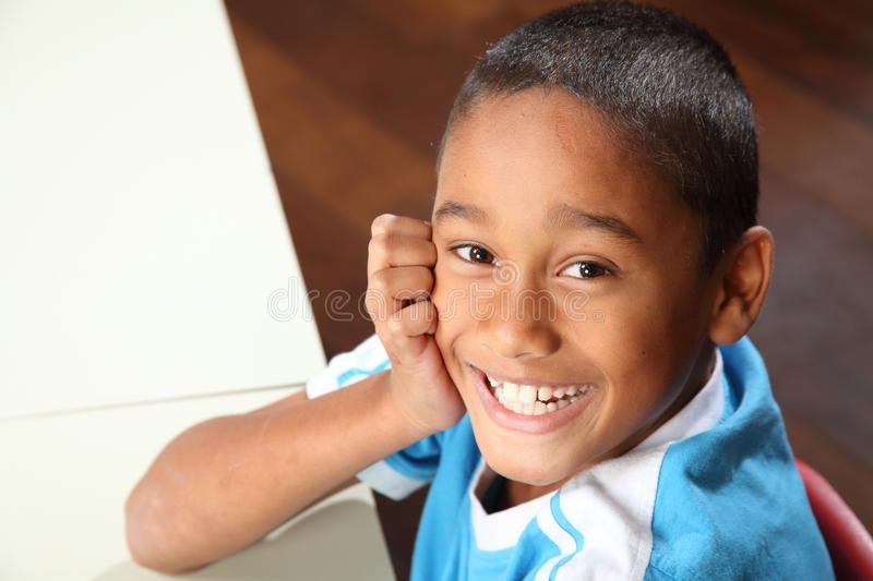 Laughing Young School Boy 9 Sitting To His Classroom Stock Photo