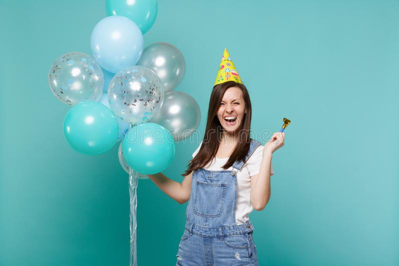 Laughing young woman in denim clothes, birthday hat holding pipe, celebrating with colorful air balloons isolated on. Blue turquoise wall background. Birthday stock image