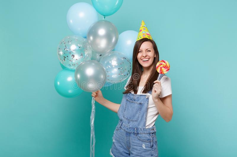 Laughing young woman in denim clothes birthday hat holding round lollipop celebrating with colorful air balloons. Isolated on blue turquoise background royalty free stock photo
