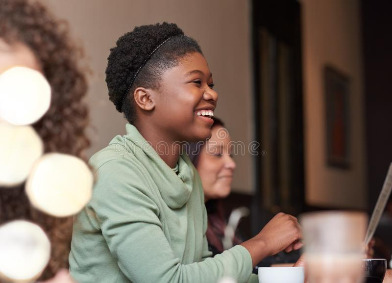 Laughing young woman hanging out with friends in a cafe royalty free stock photos