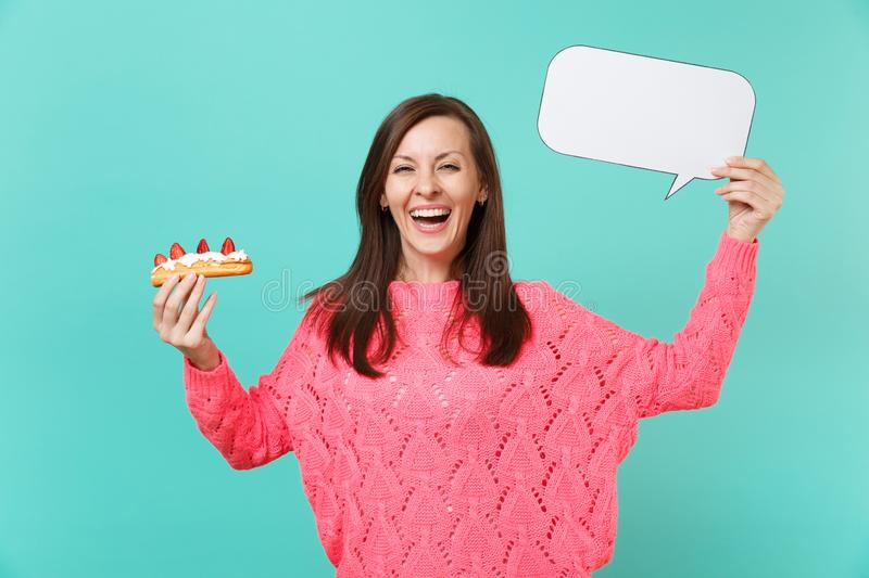 Laughing young woman in knitted pink sweater holding eclair cake, empty blank Say cloud speech bubble for promotional. Content isolated on blue background royalty free stock photo