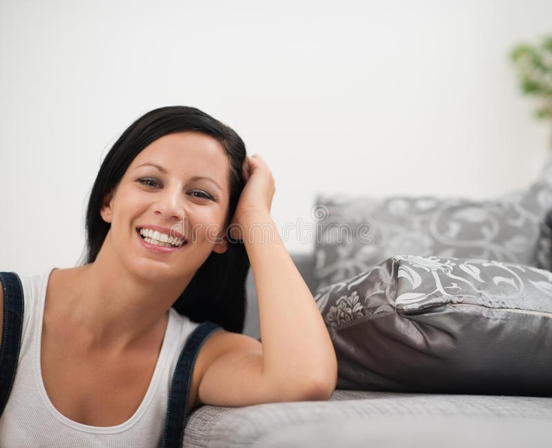 Laughing young woman sitting on floor near sofa royalty free stock photography