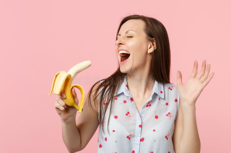 Laughing young woman in summer clothes keeping eyes closed, holding fresh ripe banana fruit isolated on pink pastel wall. Background. People vivid lifestyle royalty free stock photo