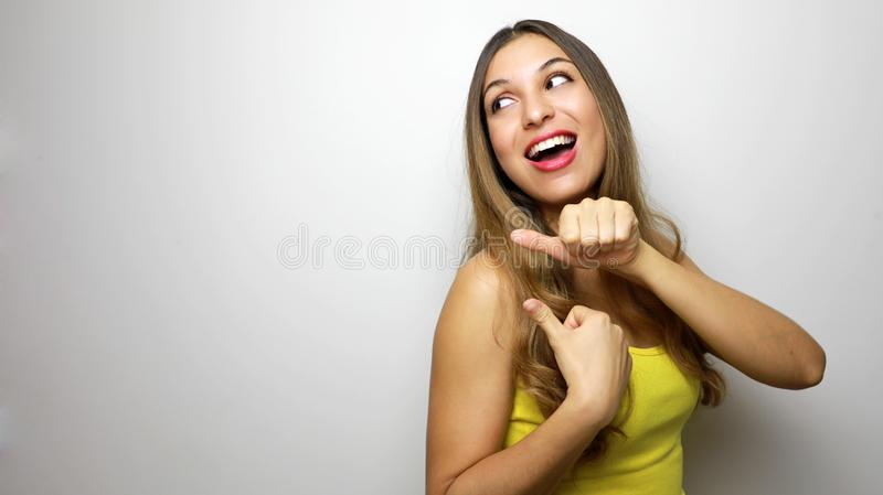Laughing young woman in yellow tank top looking and pointing away with thumbs over white background stock photography