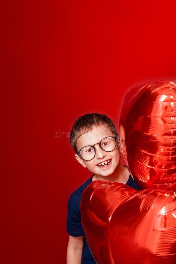 Laughting小男孩在玻璃、不同颜色心脏、星气球为情人节或生日在红色背景以自由 免版税库存图片
