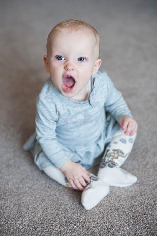 Laughting engraçado bonito e olhar do bebê na câmera Feche acima do retrato da menina no vestido cinzento imagens de stock royalty free