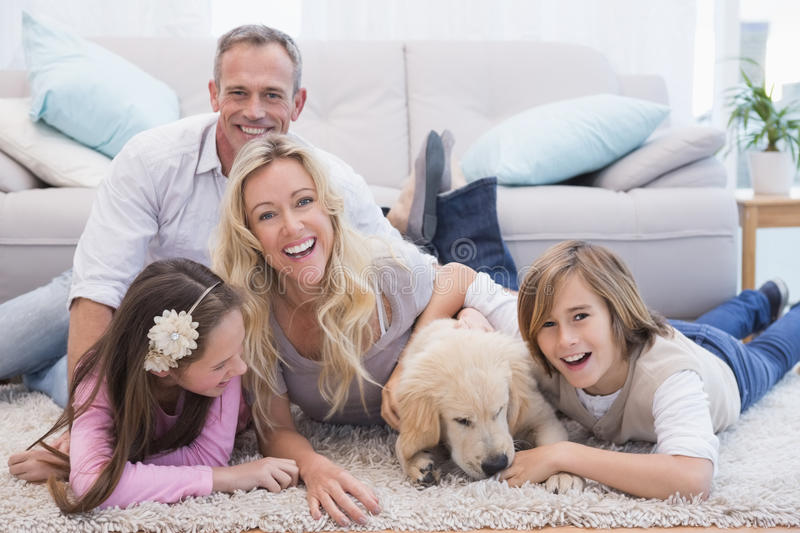 Laughting family with their pet yellow labrador on the rug royalty free stock photography
