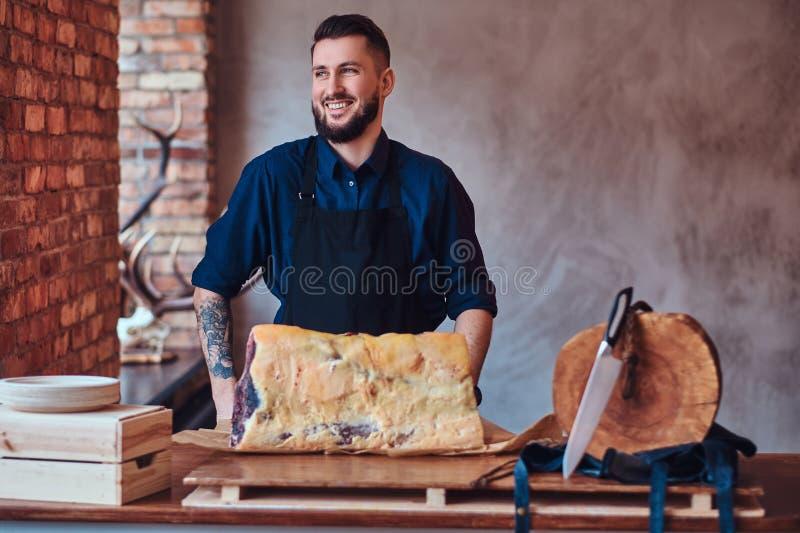 Laughting kockanseende nära en tabell med exklusivt knyckigt kött i kök med vindinre royaltyfri bild