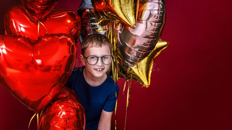 Laughting little boy in glasses, different color heart, star balloons for valentines day or birthday on red background with free stock image