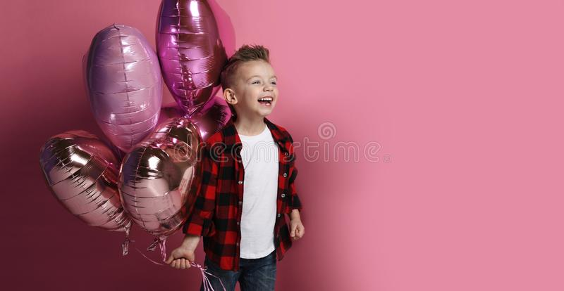 Laughting little boy with pastel color heart balloons for valentines day or birthday stock photo
