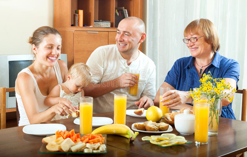 Laughting three generations family eating fresh friuts and vegitables royalty free stock photography