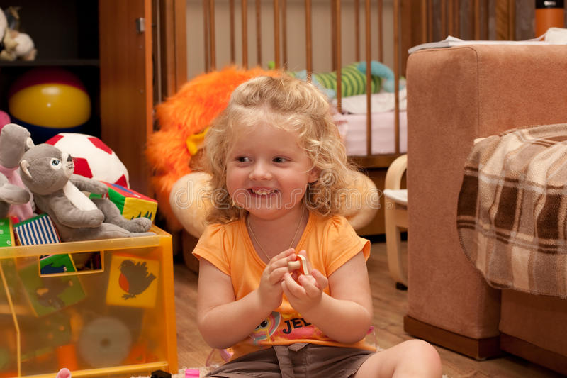 Lauhging girl on the floor in nursery room royalty free stock image