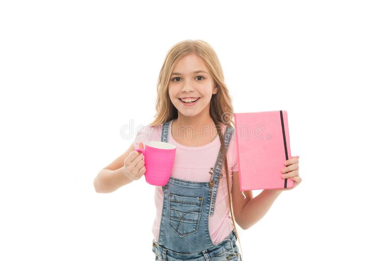 Launch your day with breakfast. Cute girl holding cup and note book. Small kid enjoying her school breakfast. Little. Baby drinking tea or milk for breakfast stock photography