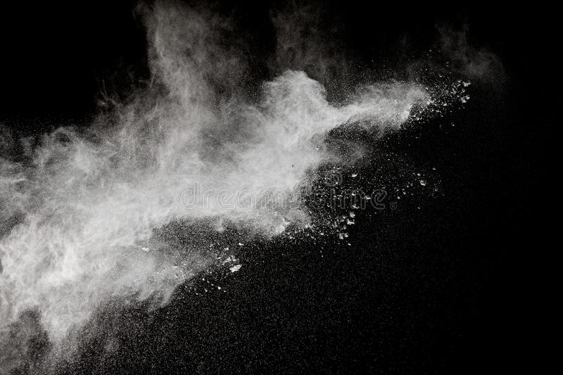 Bizarre forms of of white powder explosion cloud against dark background. Launched white particle splash on black background. Bizarre forms of of white powder stock photo