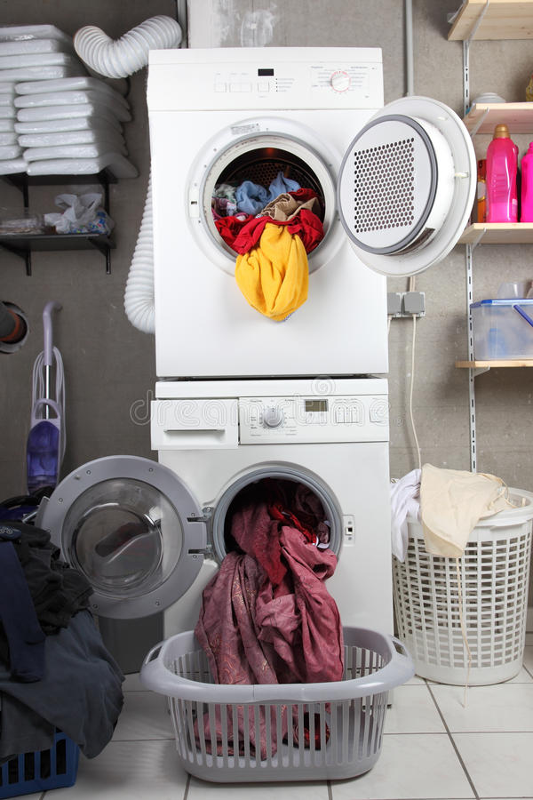 Laundry. Baskets of dirty laundry in the washing room with dryer and washing machine stock images