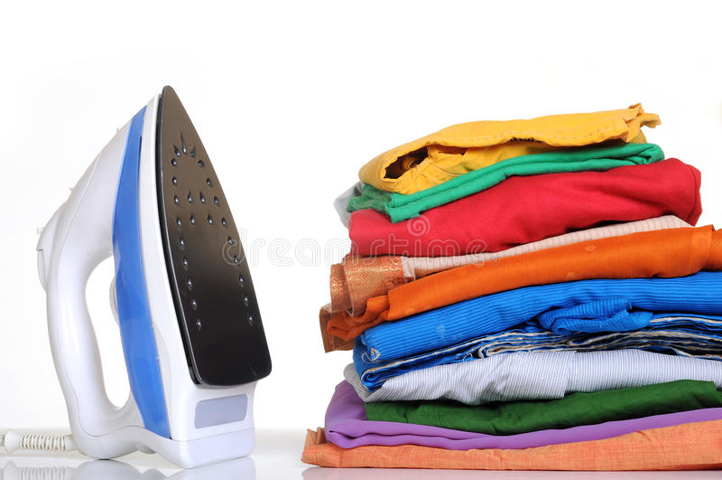 Laundry. Neatly stacked laundry dresses with iron box stock image
